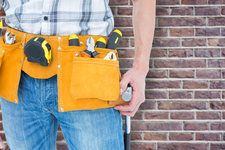 tool  belt: Technician with tool belt around waist against red brick wall