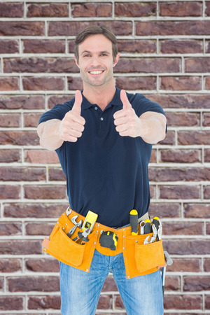 tool belt: Man wearing tool belt while showing thumbs up sign against red brick wall Stock Photo