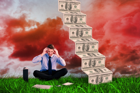 Businessman sitting on the floor with headache against green grass under red cloudy sky