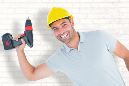 power drill: Smiling repairman holding power drill against white wall Stock Photo