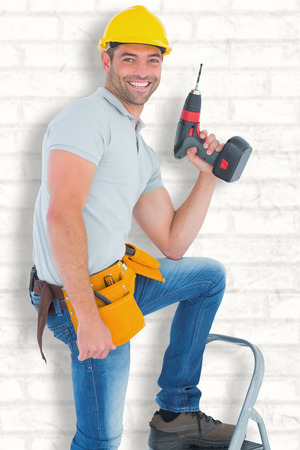 power drill: Confident handyman holding power drill while climbing ladder against white wall Stock Photo