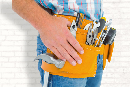 tool belt: Midsection of handyman wearing tool belt against white wall