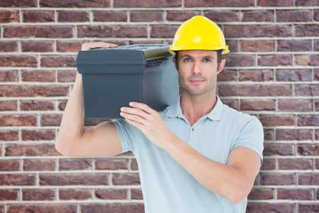 shoulder carrying: Confident worker carrying tool box on shoulder against red brick wall Stock Photo