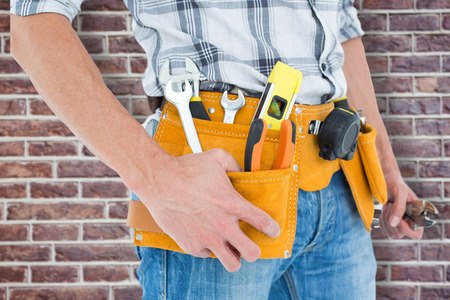 waist belt: Cropped image of technician with tool belt around waist against red brick wall