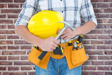 hard hat: Technician holding hammer and hard hat against red brick wall