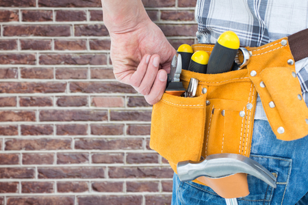 tool belt: Technician with tool belt around waist against red brick wall