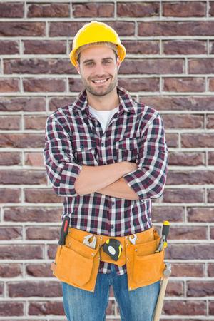 tool belt: Confident male handyman wearing tool belt against red brick wall