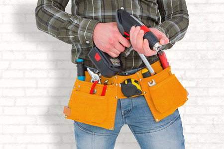 power drill: Manual worker holding gloves and hammer power drill  against white wall Stock Photo