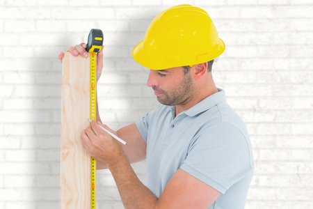 manual measuring instrument: Carpenter using measure tape to mark on wooden plank against white wall
