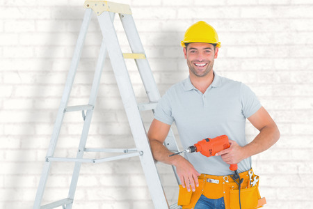 power drill: Happy handyman with power drill leaning on ladder against white wall