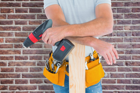 power drill: Midsection of male carpenter with power drill and plank against red brick wall