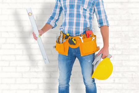 spirit level: Manual worker holding spirit level against white wall