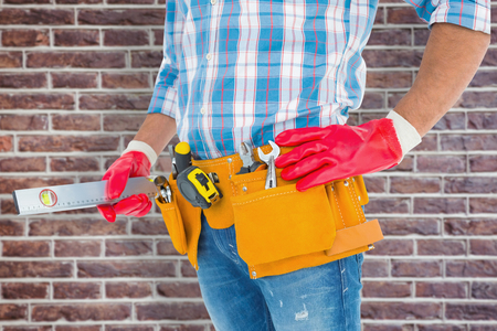 protective work wear: Midsection of handyman holding spirit level against red brick wall Stock Photo