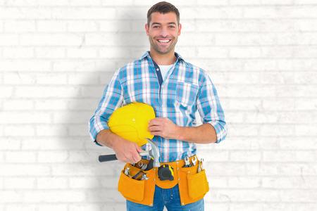hardhat: Smiling handyman holding hardhat and hammer against white wall
