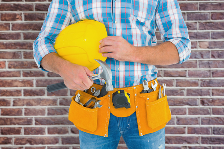 tool belt: Manual worker wearing tool belt while holding hammer and helmet against red brick wall Stock Photo