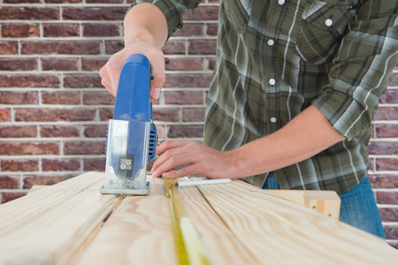 electric saw: Carpenter cutting wooden plank with electric saw against red brick wall Stock Photo