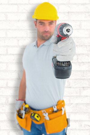 power drill: Portrait of handyman using power drill against white wall