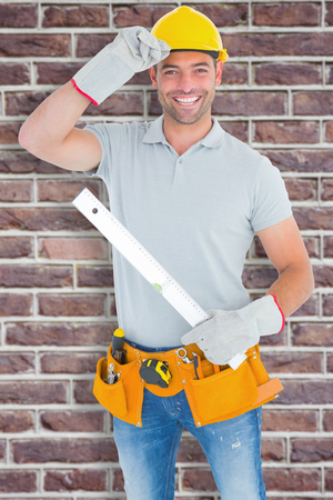 spirit level: Smiling handyman holding spirit level against red brick wall