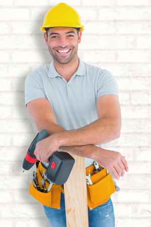 power drill: Smiling male carpenter with power drill and plank against white wall
