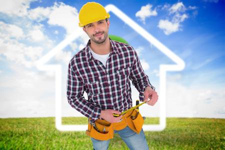 green light bulb: Smiling handyman holding tape measure  against green light bulb with white house outline