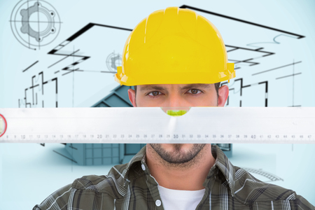 spirit level: Handyman looking at spirit level against architecture plan with house Stock Photo