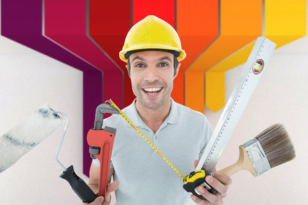 happy worker: Portrait of happy worker holding various equipment against orange red and yellow arrows