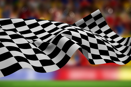 Checkered flag against blurry football pitch with crowd Stock Photo