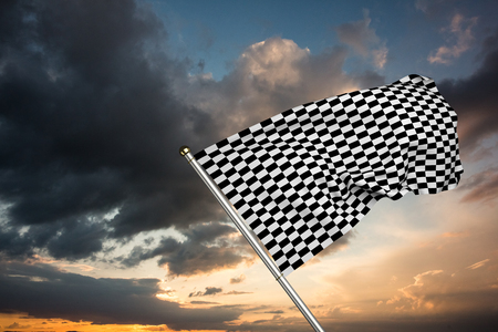 checker flag: Checkered flag against blue and orange sky with clouds Stock Photo