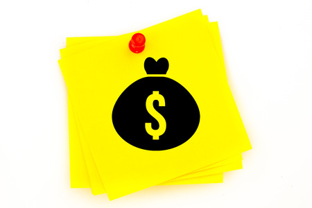 red pushpin: Money bag against sticky note with red pushpin