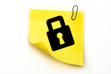 inscribe: Lock against sticky note with grey paperclip Stock Photo