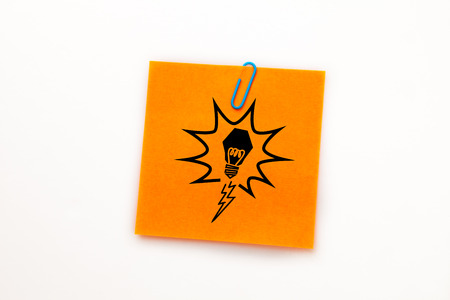 adhesive  note: Light bulb against orange adhesive note with a paperclip