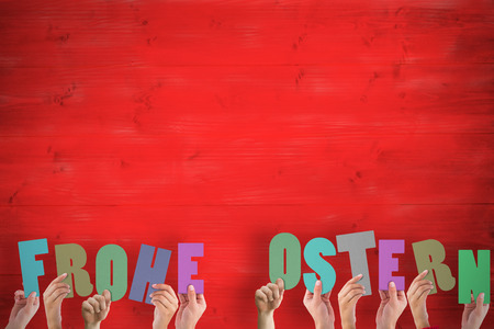 frohe: Hands holding up frohe ostern against red wooden planks