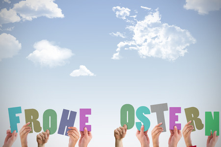 Ostern: Hands holding up frohe ostern against blue sky Stock Photo
