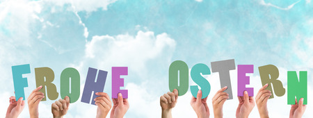 frohe: Hands holding up frohe ostern against blue sky Stock Photo