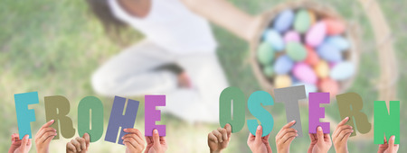 Ostern: Hands holding up frohe ostern against little girl sitting on grass showing basket of easter eggs to camera Stock Photo