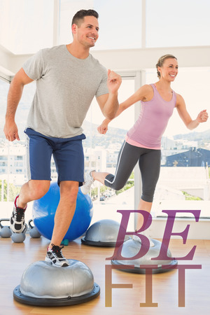 step fitness: Couple doing step aerobics in fitness studio against be fit Stock Photo