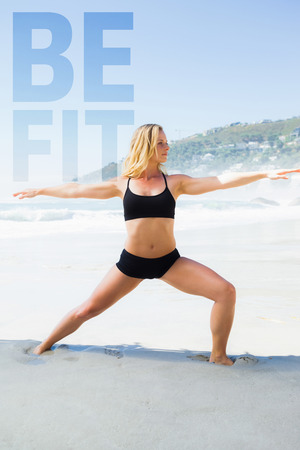 warrior pose: Fit blonde in warrior pose on the beach against be fit