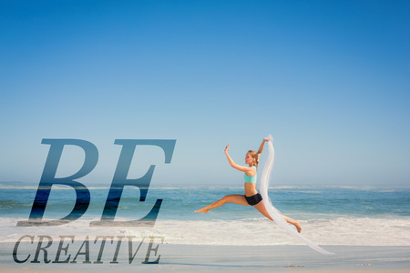 scarf beach: Fit woman jumping gracefully on the beach with scarf against be creative Stock Photo