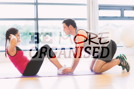 crunches: Trainer helping woman do abdominal crunches in gym against be more organised Stock Photo