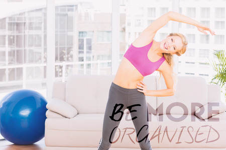 organised: Blonde smiling at camera while stretching against be more organised Stock Photo