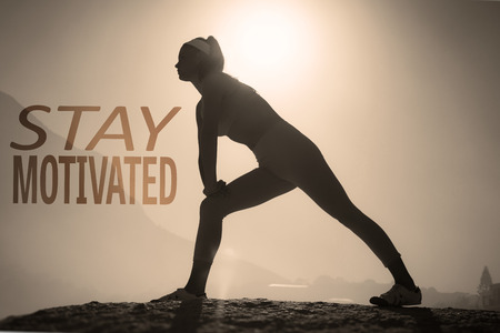 fitness motivation: Sporty blonde stretching on the beach on a rock against stay motivated