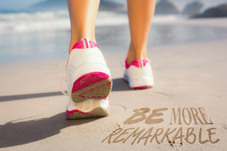remarkable: Fit woman walking on the beach against be more remarkable Stock Photo