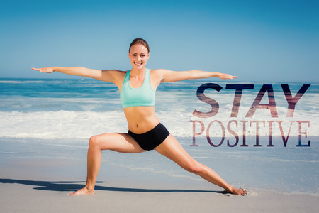 warrior pose: Fit woman standing on the beach in warrior pose against stay postive