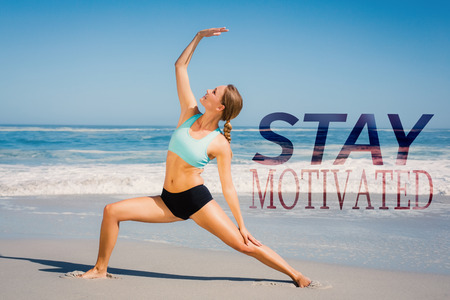 warrior pose: Fit woman standing on the beach in warrior pose against stay motivated