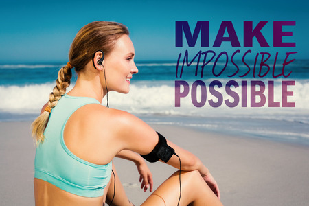 portable mp3 player: Fit woman sitting on the beach taking a break smiling  against make impossible possible