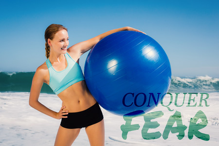 conquer: Fit woman standing on the beach holding exercise ball against conquer fear