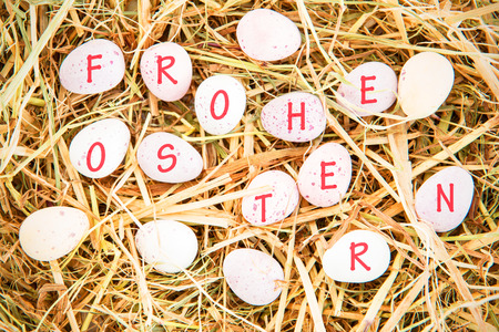 frohe: frohe ostern against little candy easter eggs on straw