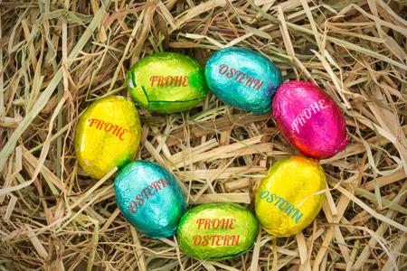 Ostern: frohe ostern against easter eggs in a circle on straw Stock Photo