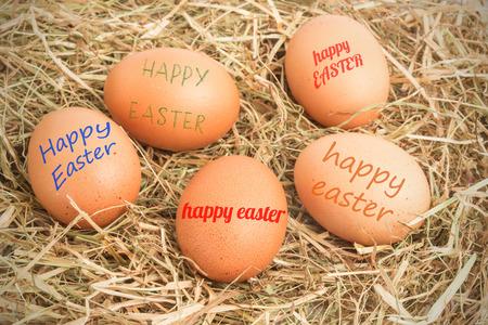 nestled: happy easter against five eggs nestled in straw