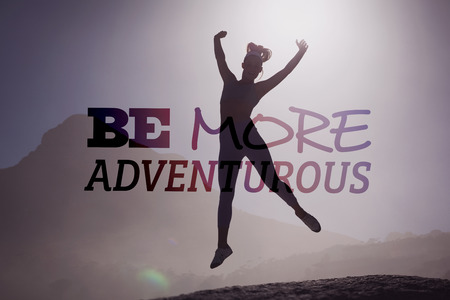 adventurous: Sporty blonde on the beach on a rock jumping against be more adventurous Stock Photo